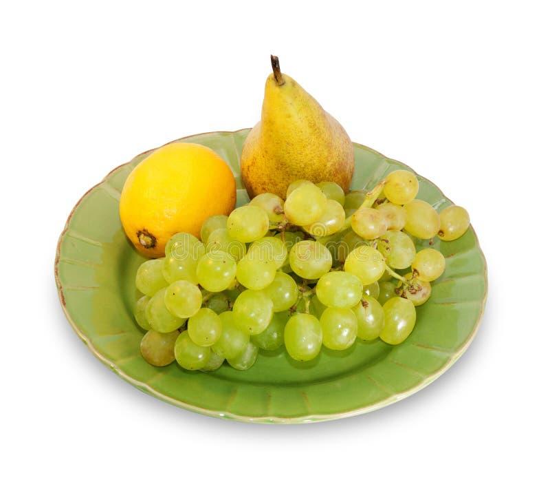 Mazzo di uva, di limone e di pera sul piatto verde isolato immagine stock libera da diritti