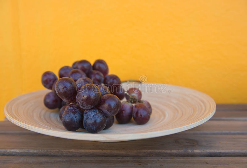 Mazzo di uva matura in piatto di legno isolato su fondo giallo fotografia stock