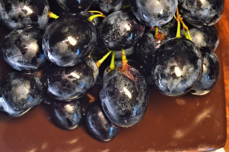 Mazzo di uva nera su un piatto marrone fotografia stock