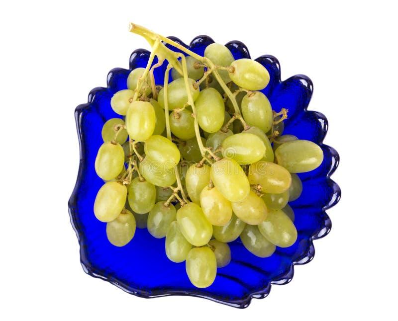 Mazzo di uva in un piatto blu fotografia stock