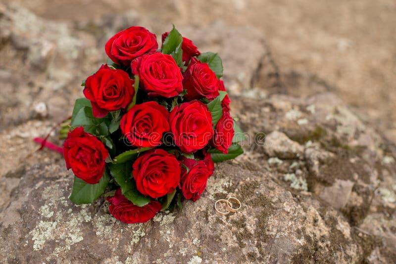 Mazzo ed anelli del fondo di nozze Il mazzo della sposa delle rose rosse sulla pietra Amore immagini stock libere da diritti