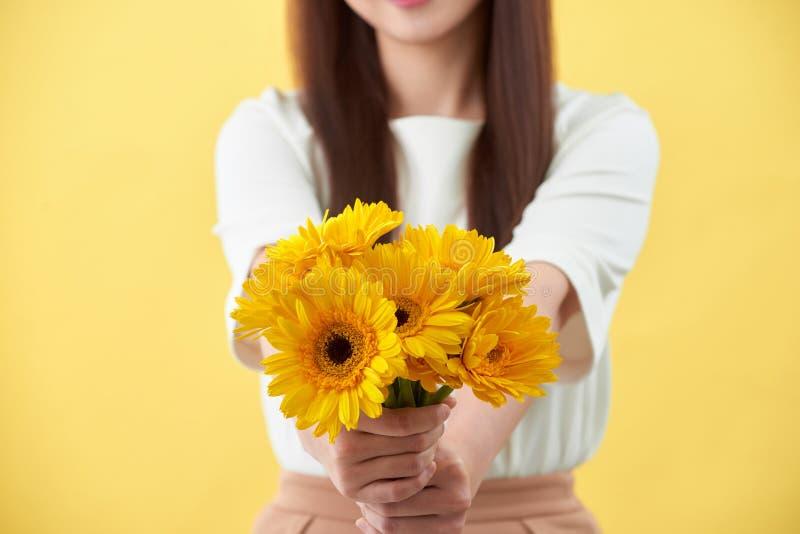 Mazzo felice della tenuta della giovane donna dei fiori in sua mano su fondo giallo fotografie stock libere da diritti