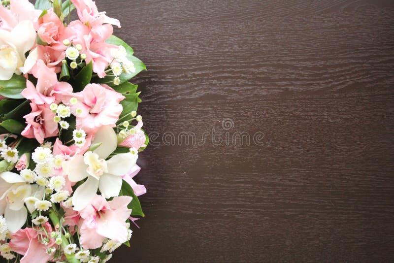 Mazzo floreale luminoso dei gigli e di una tavola di legno scura fotografia stock libera da diritti