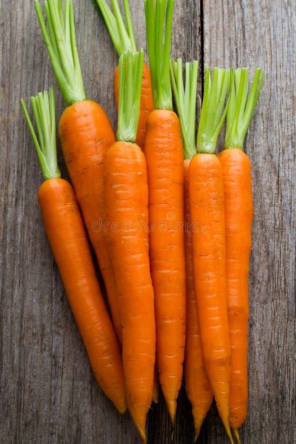 Mazzo fresco delle carote su fondo di legno rustico fotografia stock