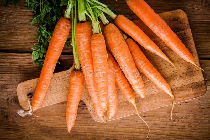 Mazzo fresco delle carote sul tagliere immagini stock