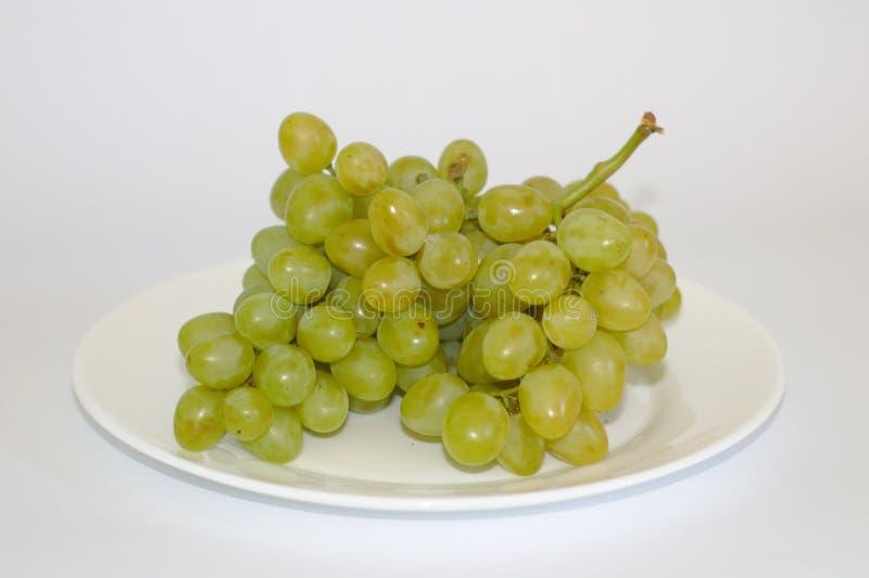 mazzo isolato di uva su un piatto fotografie stock