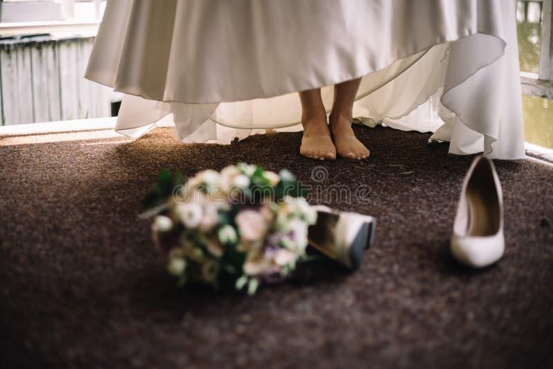 Mazzo molle del dettaglio della sposa e scarpe beige Concetto di nozze alla moda immagine stock