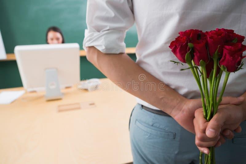 Mazzo nascondentesi dell'uomo davanti alla donna di affari allo scrittorio fotografie stock libere da diritti