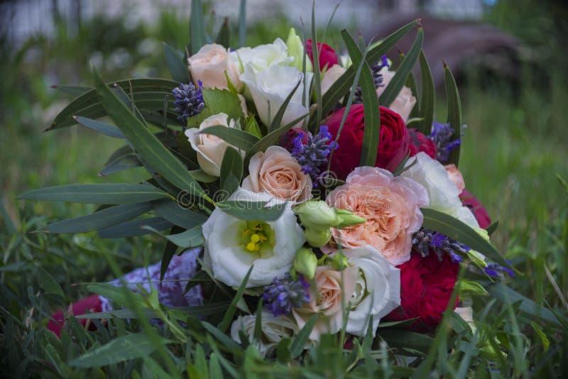 Mazzo nuziale della sposa nell'erba verde di luglio immagini stock libere da diritti