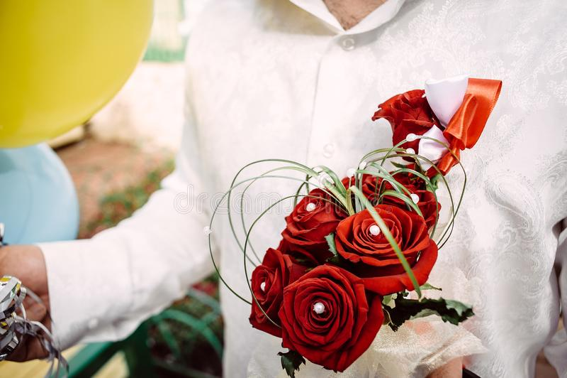 Mazzo nuziale delle rose rosse nelle mani dello sposo immagine stock