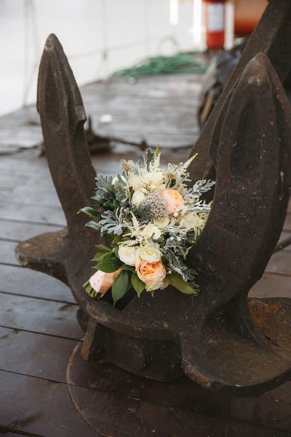 Mazzo nuziale di nozze delle rose, crisantemi, eucalyptus, propping sull'ancora della nave fotografia stock libera da diritti