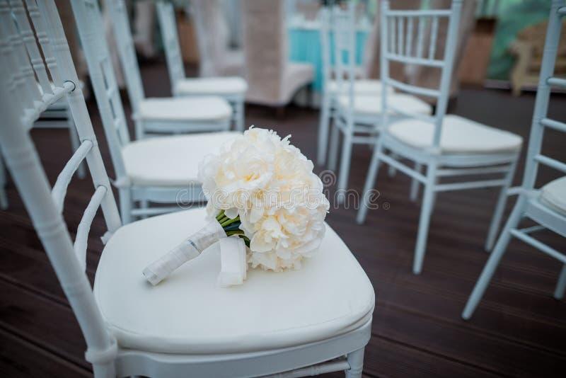 Mazzo nuziale sulla sedia bianca, decorazione di nozze immagini stock