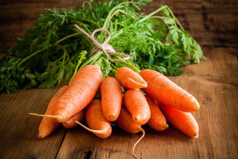 Mazzo organico fresco delle carote su fondo di legno fotografie stock