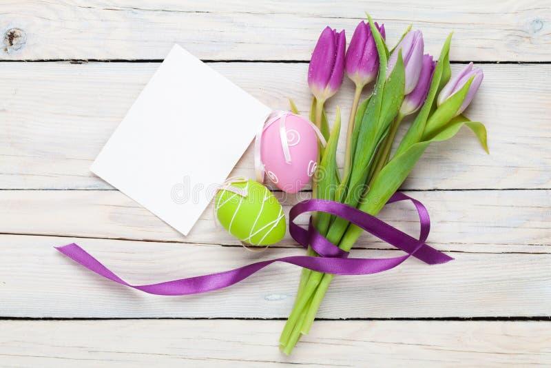 Mazzo porpora del tulipano, uova di Pasqua e cartolina d'auguri in bianco fotografie stock