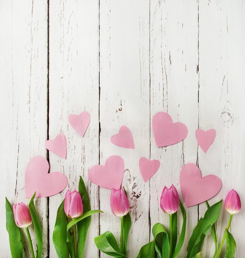 Mazzo rosa dei tulipani con i cuori di carta su fondo di legno fotografie stock