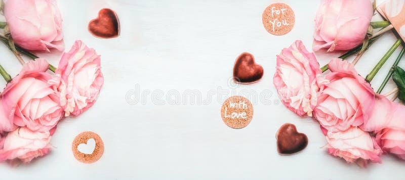 Mazzo rosa romantico delle rose con cioccolato nella forma di cuore e carte con iscrizione con l'amore per voi su fondo di legno  immagini stock libere da diritti