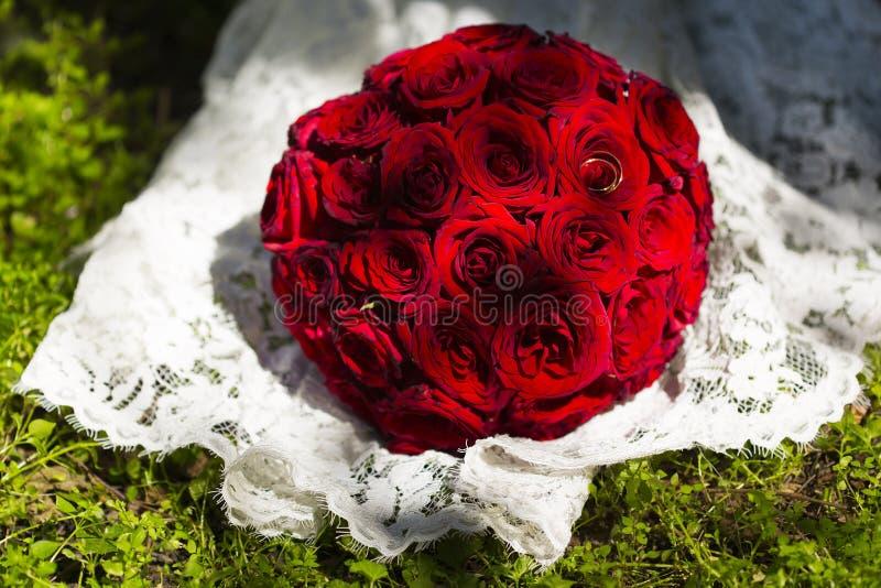 Mazzo rotondo di nozze delle rose rosse o cremisi sul vestito da sposa dal pizzo immagini stock libere da diritti