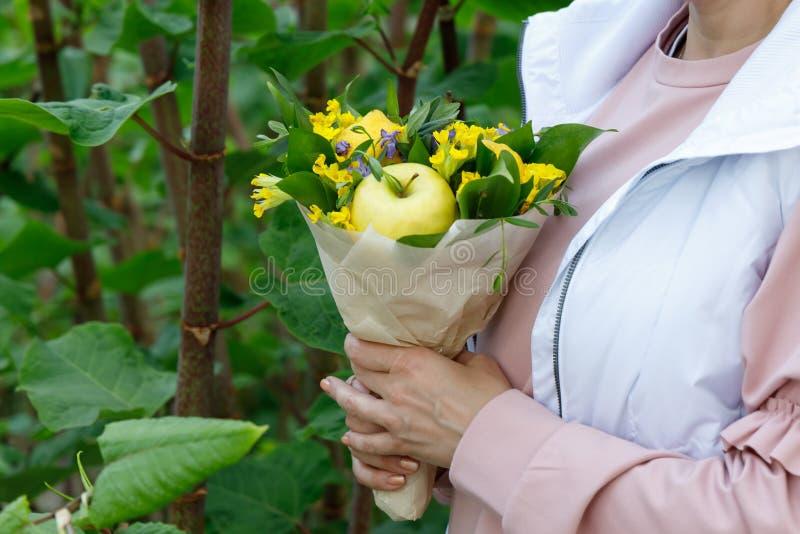 Mazzo sveglio dei fiori e dei frutti nelle mani di una giovane donna su un fondo di fogliame verde fotografia stock