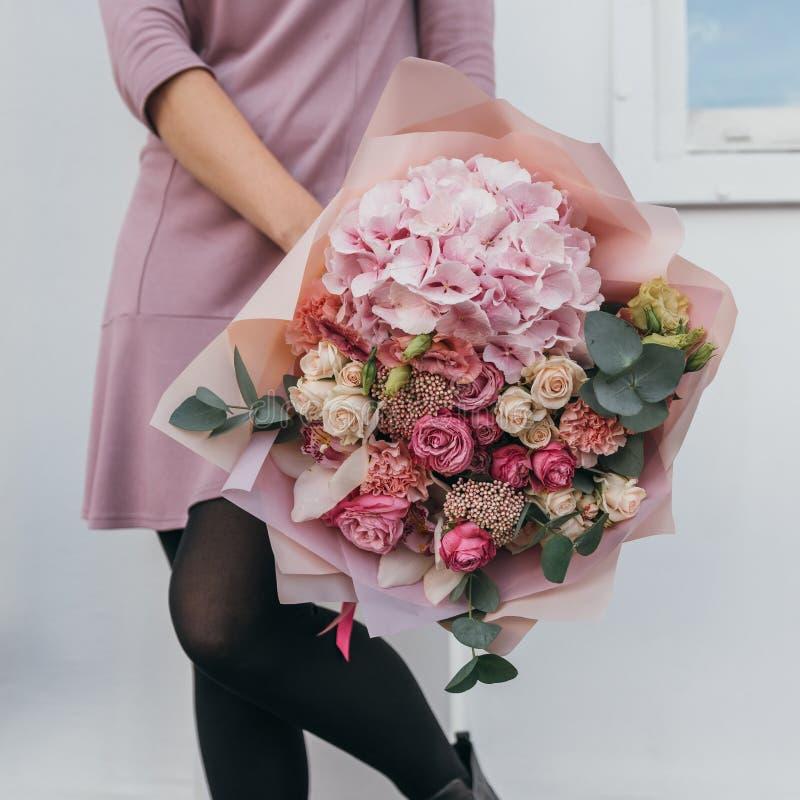 Mazzo variopinto dei fiori freschi differenti nelle mani della donna del fiorista Fondo rustico del fiore Mazzo del mestiere di fotografia stock libera da diritti