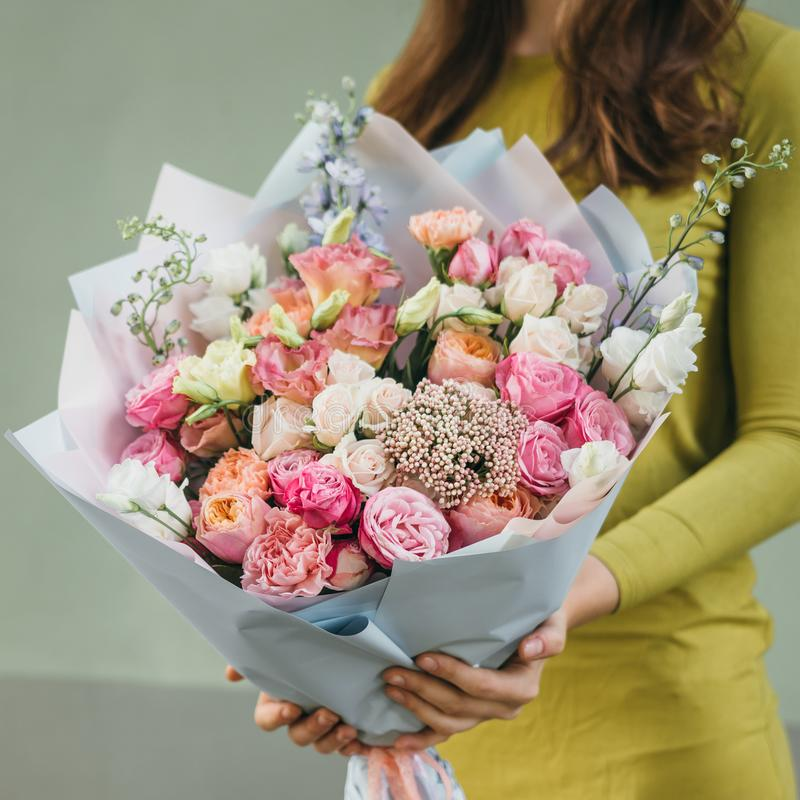 Mazzo variopinto dei fiori freschi differenti nelle mani della donna del fiorista Fondo rustico del fiore Mazzo del mestiere di immagini stock