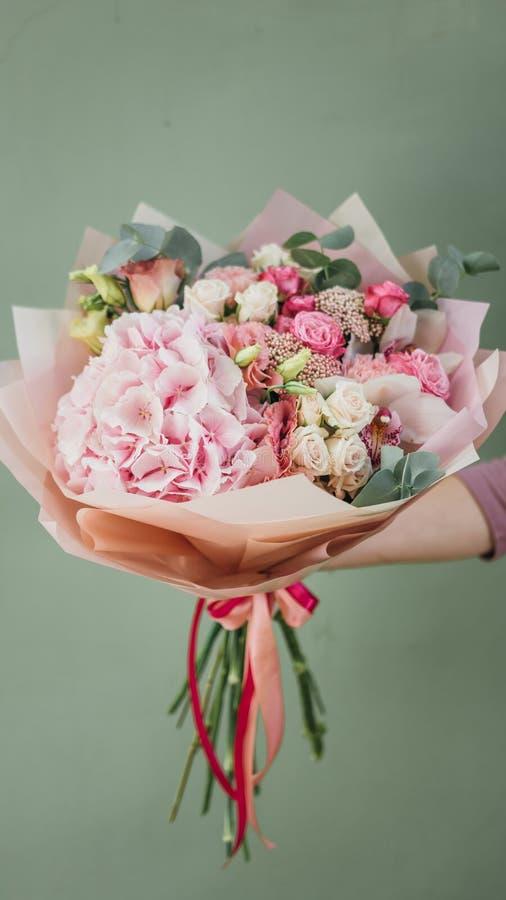 Mazzo variopinto dei fiori freschi differenti nelle mani della donna del fiorista Fondo rustico del fiore Mazzo del mestiere di fotografia stock