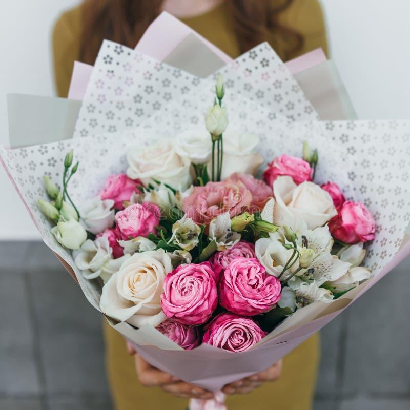 Mazzo variopinto dei fiori freschi differenti nelle mani della donna del fiorista Fondo rustico del fiore Mazzo del mestiere di immagine stock libera da diritti
