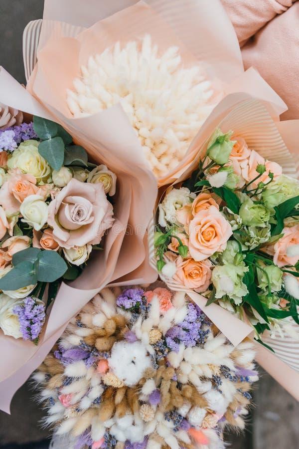 Mazzo variopinto dei fiori secchi differenti del ramo secco dei fiori nelle mani della donna del fiorista Fondo rustico del fiore fotografia stock libera da diritti