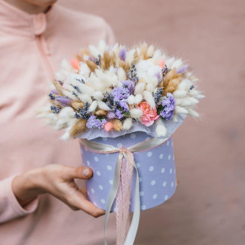 Mazzo variopinto dei fiori secchi differenti del ramo secco dei fiori nelle mani della donna del fiorista Fondo rustico del fiore immagine stock libera da diritti