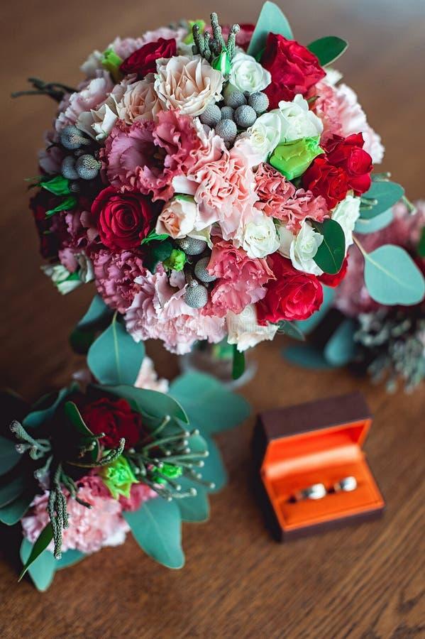 Mazzo variopinto di nozze con le rose ed i garofani sulla tavola accanto al Boutonniere delle damigelle d'onore e sulla scatola c immagine stock libera da diritti