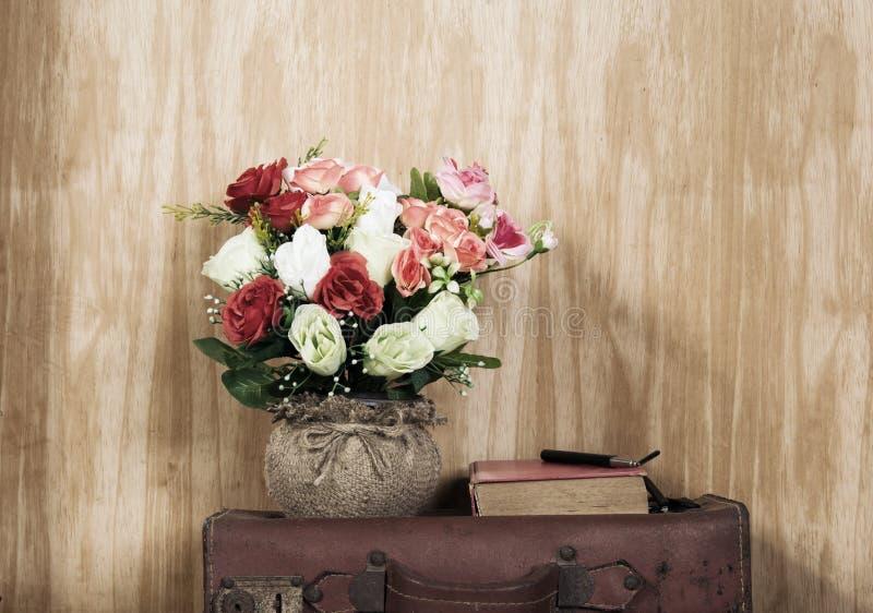 Mazzo in vecchio vaso sulla borsa vecchia e sul libro fotografia stock libera da diritti