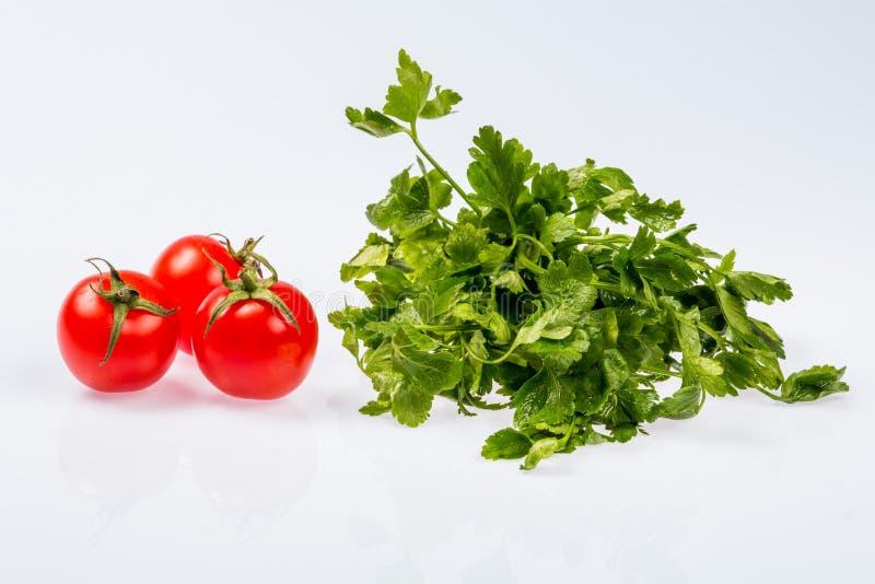 Mazzo verde fresco maturo di prezzemolo con tre pomodori, ingrediente brillante su fondo bianco immagine stock libera da diritti