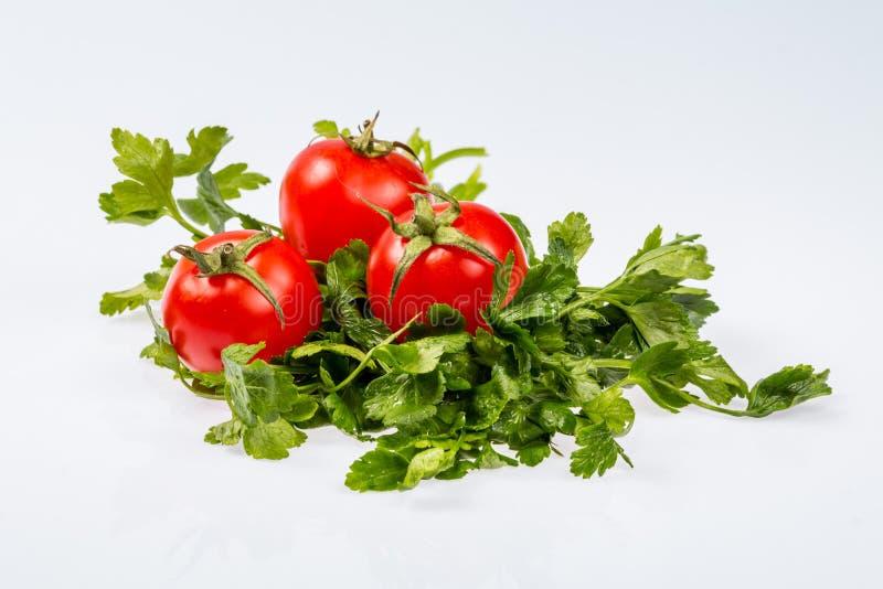 Mazzo verde fresco maturo di prezzemolo con tre pomodori, ingrediente brillante su fondo bianco immagini stock libere da diritti