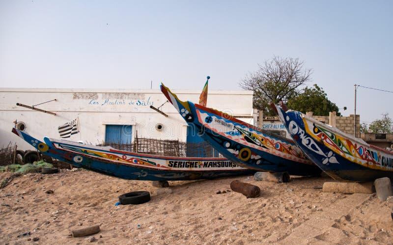 Mbour, Sénégal : Bateaux de pêche colorés échoués dans le sable images stock