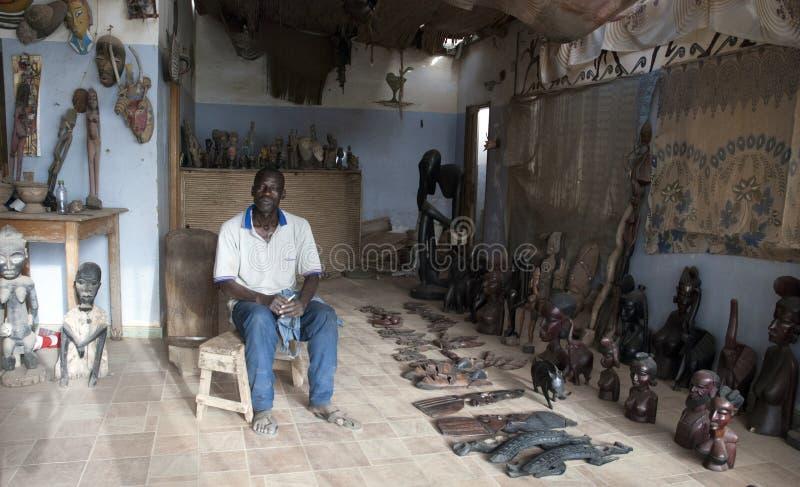 Mbour Senegal, handcrafts säljaren som poserar inom hans lilla souvenir, shoppar royaltyfri foto