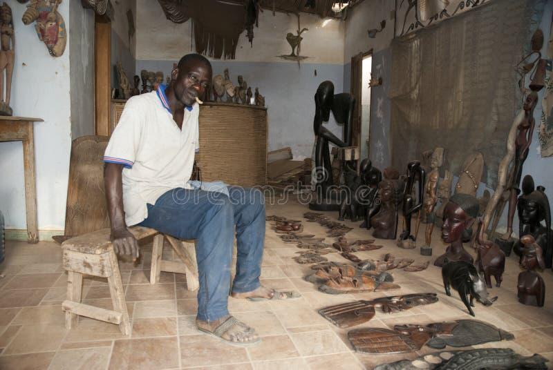 Mbour Senegal, handcrafts säljaren som poserar inom hans litet, shoppar arkivbild