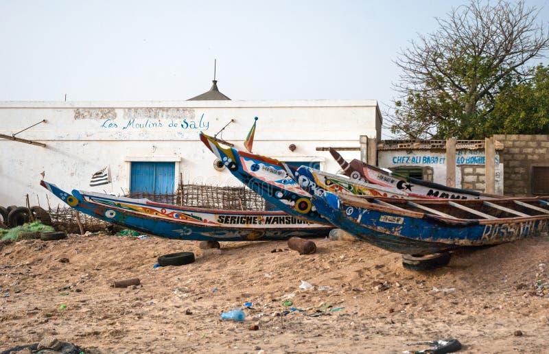 Mbour, Senegal: Kleurrijke die vissersboten in het zand zijn vastgelopen stock afbeelding