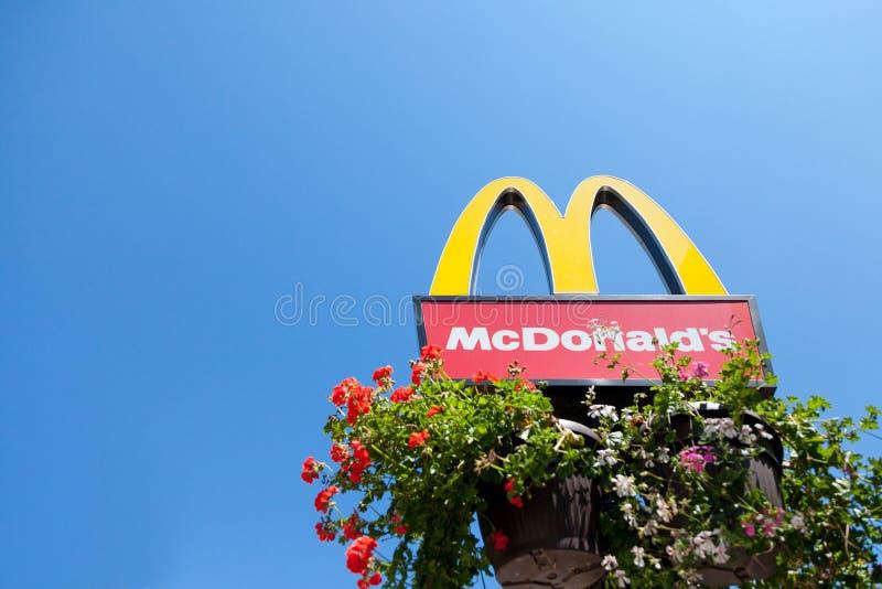 Mc Donald ` s embleem met zijn iconisch M met een blauwe hemelachtergrond en sommige bloemen bij zijn bodem royalty-vrije stock foto