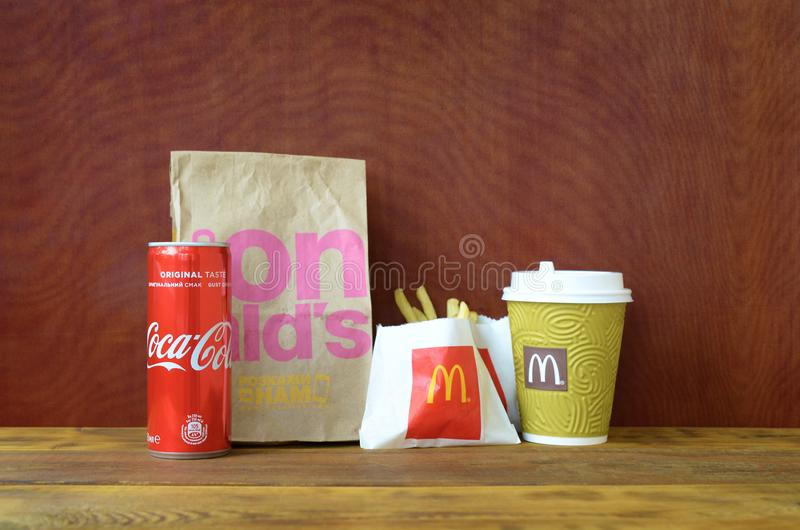 McDonald`s take away paper bag and french fries with coca cola can on wooden table royalty free stock photo