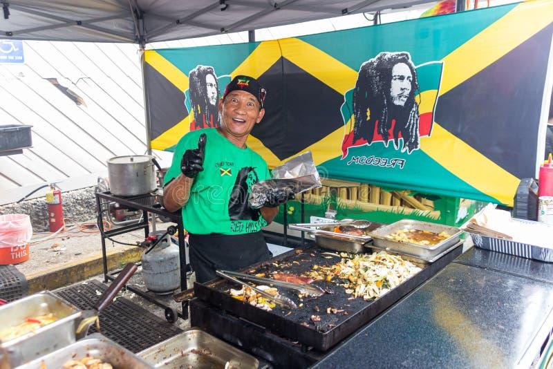 2019 McDonough, Georgia Geranium Festival - Cooking Jamaican Food. McDonough, Georgia - May 18, 2019: A food vendor prepares Jamaian food for customers at the royalty free stock photography