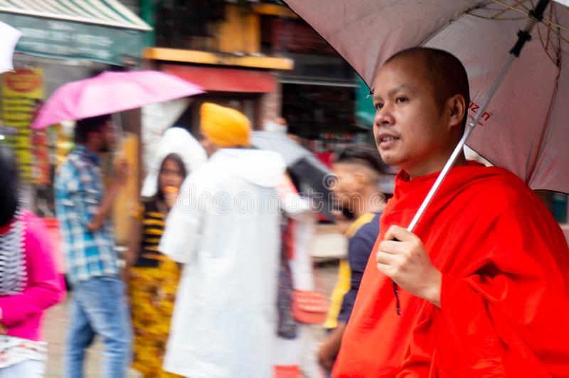 Monk in orange clothes and an umbrella walking the streets in Dharamshala royalty free stock photography