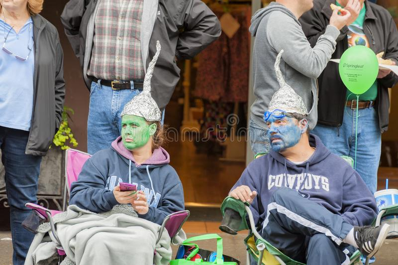 Annual UFO Festival in McMinnville Oregon. McMinnville, Oregon, USA - May 16, 2015: A couple wearing foil point hats with painted faces sit along the curb of stock image