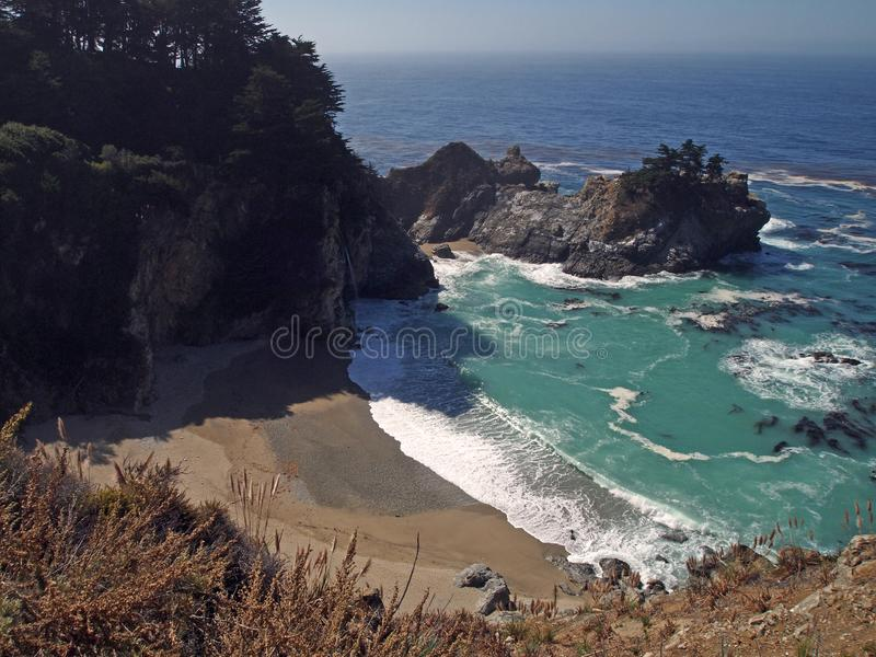 McWay Cove with McWay Falls. McWay Cove, a beach with a waterfall on the coast of Big Sur that flows from McWay Creek in Julia Pfeiffer Burns State Park directly royalty free stock photo
