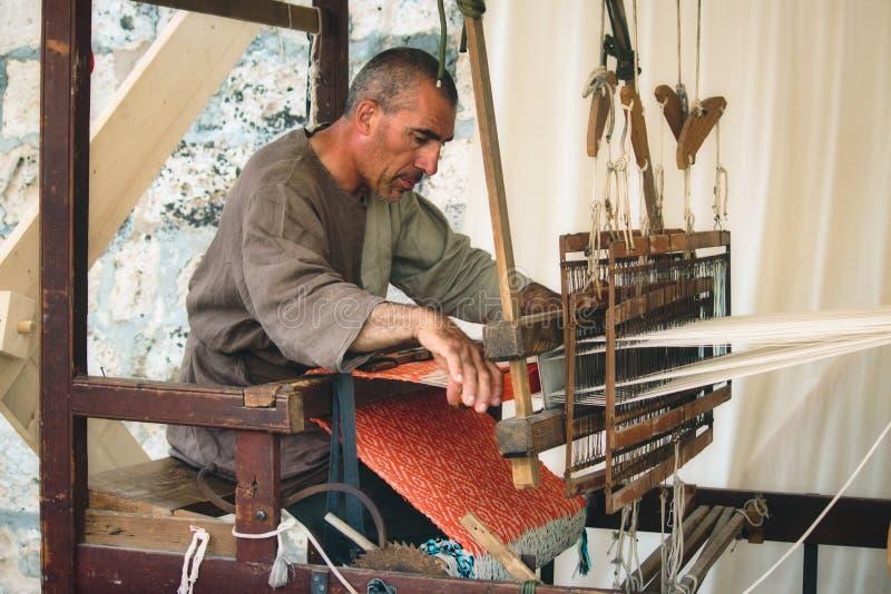 MDINA/MALTA - 4 DE MAYO DE 2019: Hombre con un telar del piso del pie-pedal para tejer el paño imágenes de archivo libres de regalías