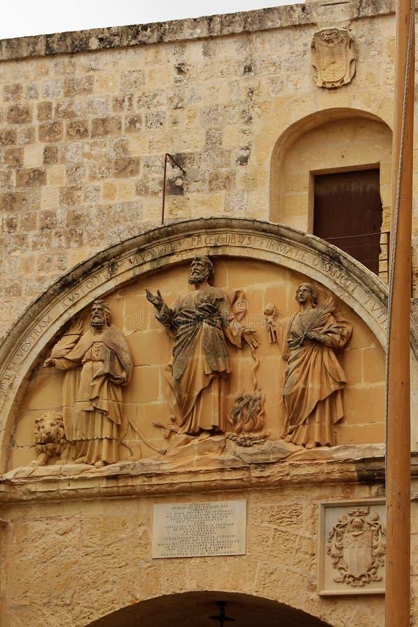 Mdina, Malta, Juli 2014 Fragment van de oude steenmuur met het beeld van de drie heiligen stock fotografie