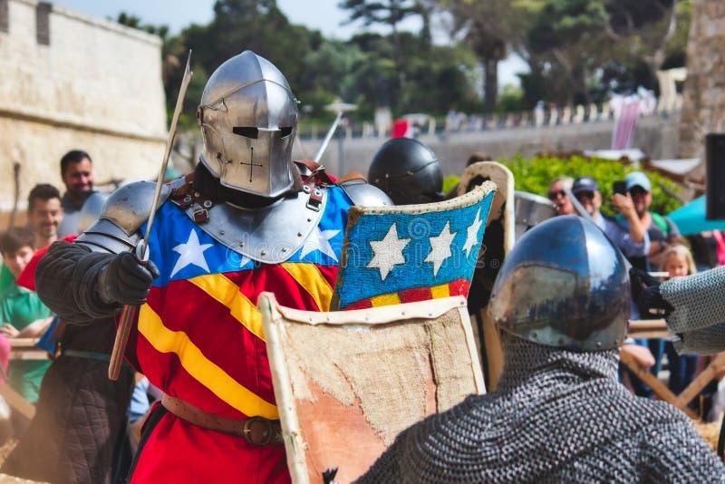 Mdina/Malta - Maj 4 2019: Män som kläs som riddare i harnesken som är beträffande - anta en strid på en medeltida festival royaltyfria foton