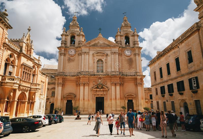 MDINA, MALTA - SEPTEMBER, 15 2018: Beautiful famous Saint Poul Cathedral in Mdina town, Malta at nice sunny day with a group of. Tourists near stock photo