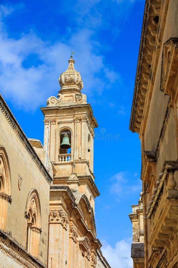 Mdina Malta Smal gata med kyrkliga klockstapel- och för byggnadssten fasader på bakgrund för blå himmel royaltyfri foto