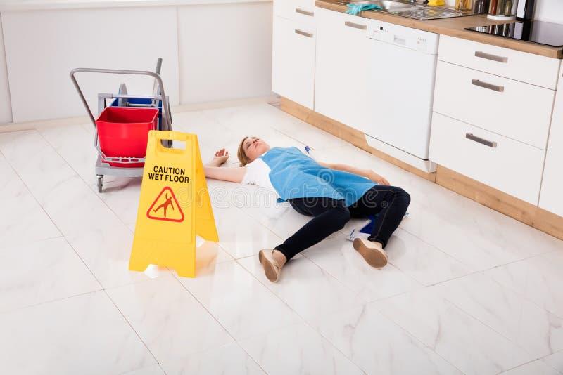 Mdlejący Housemaid lying on the beach Na podłoga W kuchni zdjęcie stock