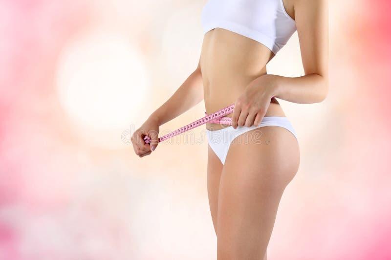 Meça a dieta no fundo do rosa da barriga da mulher fotos de stock royalty free