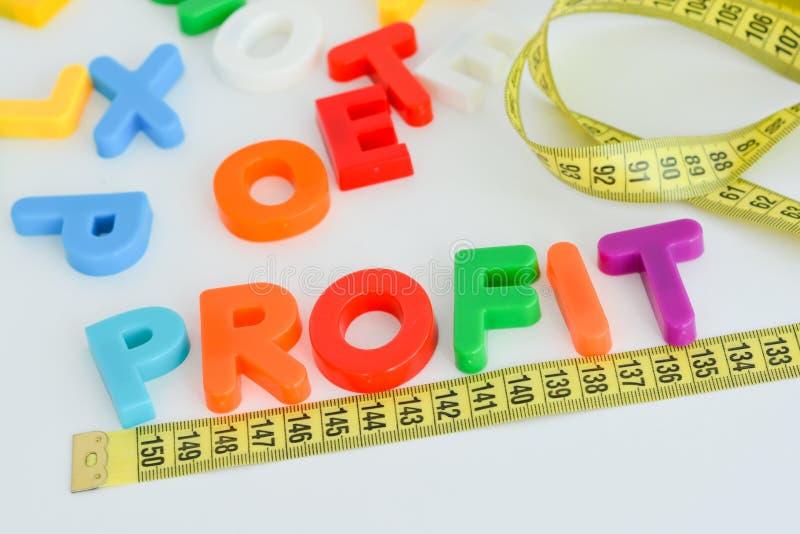 Meça seu conceito do lucro escrito com blocos coloridos magnéticos da letra com fita de medição fotos de stock royalty free